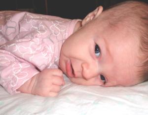 Baby lying on tummy looking sad
