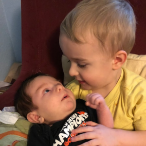 Baby brother snuggling on older brother's lap.