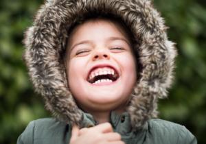 Girl laughing wearing a fur coat.