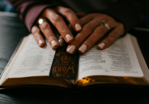 Woman's hands on top of open Bible.