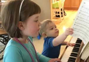 Boy and girl playing piano together